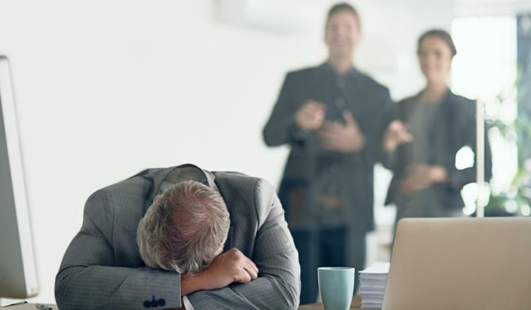 Man with mental health issue slumped on his desk while co-workers look on